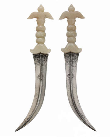 Rare and unusual Asian daggers with curved steel blade ivory handle gold decorated pins isolated on white