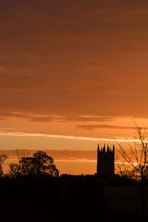 English church tower at early morning sunrise with a red and yellow sky