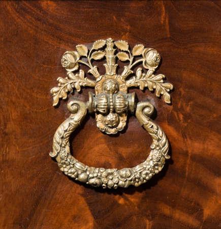 Antique brass elaborate handle on wood background 免版税图像