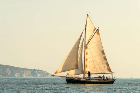 Old sailing boat all sails on the sea with setting sun 免版税图像 - 131363842