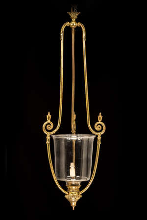 Vintage shaped brass hanging light pendant isolated on black background