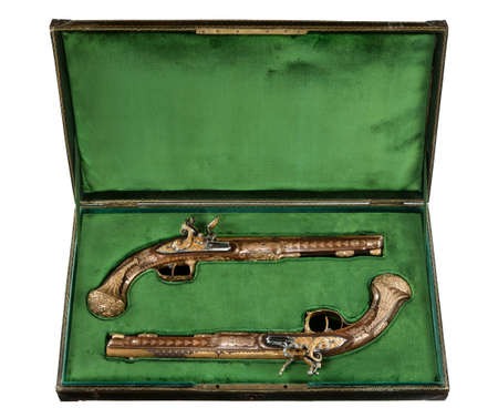 A pair of vintage flintlock pistols highly ornate in their case isolated on white.