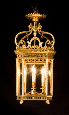 Antique decorative hanging electric brass hall lantern light illuminated glowing isolated on black