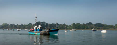 Old small English commercial fishing boat leaving to go to sea