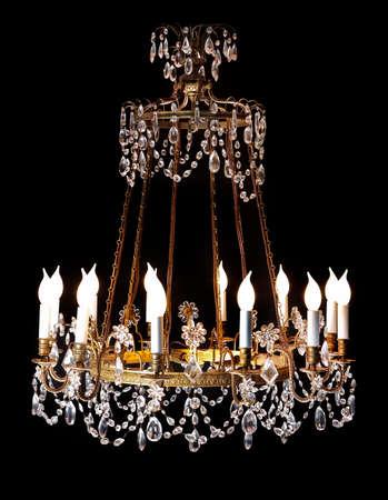 Large vintage original crystal chandelier isolated on black background. 免版税图像