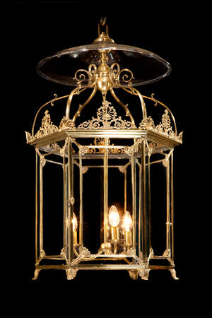 Antique decorative hanging brass hall lantern lamp illuminating isolated on black