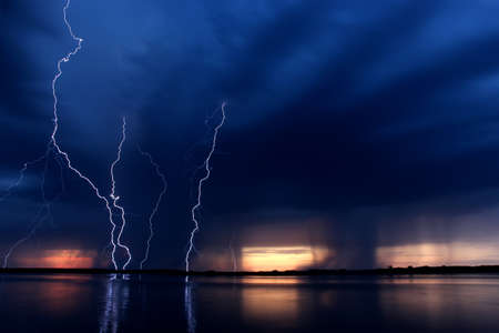 summer thunderstorm with lightning at sunset reflected in lake Stock Photo - 9991851