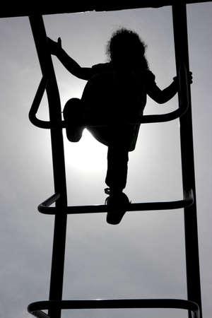 Un enfant qui grimpe à une échelle silhouettée contre le ciel Banque d'images - 9991852