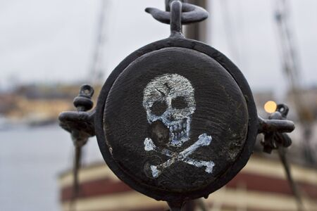 mast: Pirate label. The skull and crossbones painted on the side of the mast of the ship