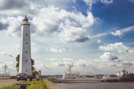 outpost: Panoramic view of the August sun, with Kronstadt promenade to the pier with a lighthouse and ships. To the left stands a tall white lighthouse, to the right landing warships