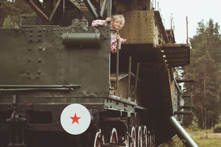 outpost: Girl in a pink jacket on a 305-mm installation TM-3-12 on the military-historical site of Fort Krasnaya Gorka Stock Photo