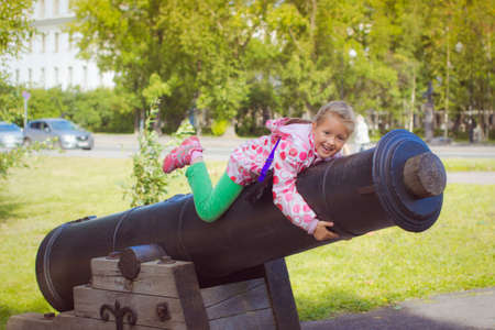 outpost: Girl in a bright pink jacket, sitting on an old cannon on the ships promenade in Kronstadt Stock Photo