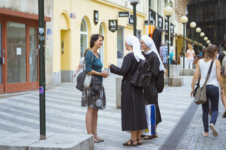 nuns: PRAGUE, CZECH REPUBLIC - AUGUST 28, 2015: Woman talking with two nuns in the old town of Prague, Czech Republic