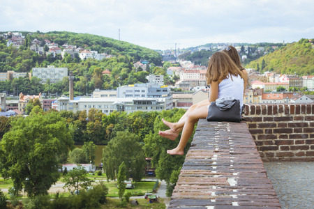 dangling: PRAGUE, CZECH REPUBLIC - AUGUST 28, 2015: Two girls sitting on the edge of the wall, his feet dangling. View from Vysehrad national cultural monument - the Old burgraves office in the district of Vysehrad Prague, Czech Republic