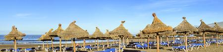 the americas: TENERIFE, SPAIN - JANUARY 13, 2013: Straw umbrellas and loungers on the Playa de Las Americas, Tenerife, Canary Islands, Spain