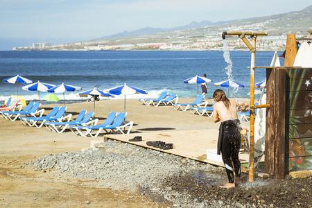 junge nackte m�dchen: TENERIFE, SPANIEN - 13. Januar 2013: M�dchen-Surfer W�sche in der Dusche. Beliebte kanarische Resort Playa de Las Americas, Teneriffa, Kanarische Inseln, Spanien Editorial