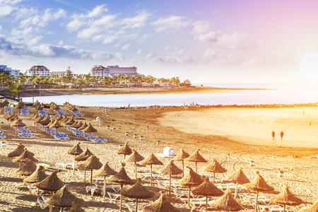 enero: TENERIFE, ESPAÑA - 14 de enero 2013: sombrillas de paja y tumbonas en la Playa de Las Americas, Tenerife, Islas Canarias, España Editorial