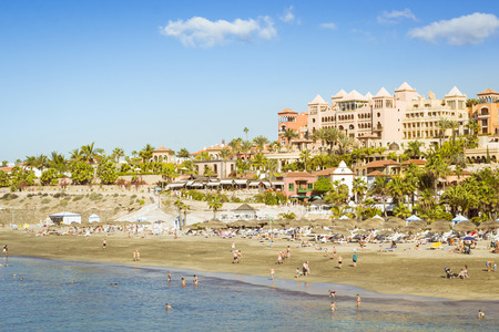 adeje: TENERIFE, SPAIN - JANUARY 14, 2013: Sandy beach with thatched parasols and sunbeds, Costa Adeje, Tenerife, Canary Islands, Spain
