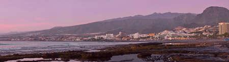 the americas: TENERIFE, SPAIN - JANUARY 14, 2013: Bright sunset on the coast, popular canarian resort Playa de Las Americas, Tenerife, Canary Islands, Spain