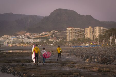the americas: TENERIFE, SPAIN - JANUARY 14, 2013: Surfers surf on the waves, bright sunset on the coast in the popular canarian resort Playa de Las Americas, Tenerife, Canary Islands, Spain