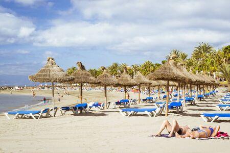 the americas: TENERIFE, SPAIN - JANUARY 18, 2013: Straw umbrellas and loungers on the Playa de Las Americas, Tenerife, Canary Islands, Spain Stock Photo