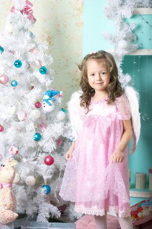 magie: En attendant No�l: une belle petite fille avec une cure de jouvence d'hiver dans une robe rose d�core le nouvel arbre de l'ann�e sur le fond de style de nouvelles d�corations de l'ann�e dans le style de high key
