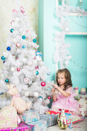 girl pose: Waiting for Christmas: a beautiful little girl with a winter makeover in a pink dress decorates the new year tree on the background of stylish new year decorations in the style of high key