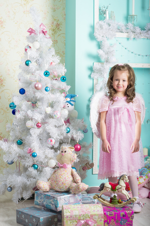 decorates: Waiting for Christmas: a beautiful little girl with a winter makeover in a pink dress decorates the new year tree on the background of stylish new year decorations in the style of high key