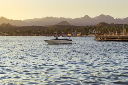 el sheikh: SHARM EL SHEIKH, EGYPT - FEBRUARY 28, 2014: Boat near a wooden pier on the beach in the evening, red sea coast from the hotel beach Albatros resort, Sharm El Sheikh, Egypt