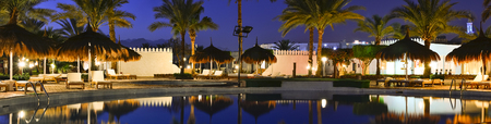 sharm: SHARM EL SHEIKH, EGYPT - FEBRUARY 27, 2014: February night on the beach, straw umbrellas and sunbeds by the pool at the hotel beach Albatros resort, Sharm El Sheikh, Egypt Editorial