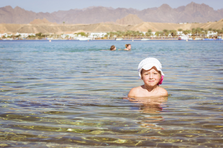 little girl beach: SHARM EL SHEIKH, EGYPT - MARCH 1, 2014: Girl in white hat sitting in a water in the middle of the beach, red sea coast, hotel beach Albatros resort, Sharm El Sheikh, Egypt