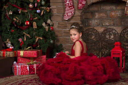 newyear: Cute girl in red dress holding Christmas gift on the background of a magical New-year interior with burning fireplace and decorated Christmas tree Stock Photo
