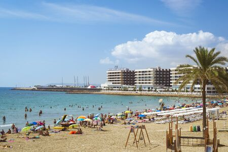 ALICANTE, SPAIN - SEPTEMBER 9, 2014: Sunny beach Playa del Postiguet near the castle Santa Barbara. Tourists relax under umbrellas on the warm sand. Alicante, Valencian Community, Spain