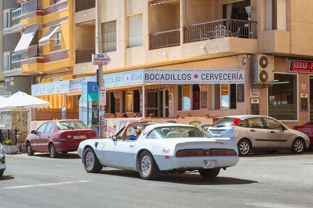 av: TORREVIEJA, SPAIN - SEPTEMBER 13, 2014: White modern sport-car on sunny street, Av Doctor Mariano Ruiz Canovas, Torrevieja, Valencia, Spain