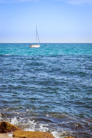 av: TORREVIEJA, SPAIN - SEPTEMBER 13, 2014: Sailboats floating in sea on horizon, coast of Sunny beach, Av de los Marineros, Torrevieja, Valencian Community, Spain