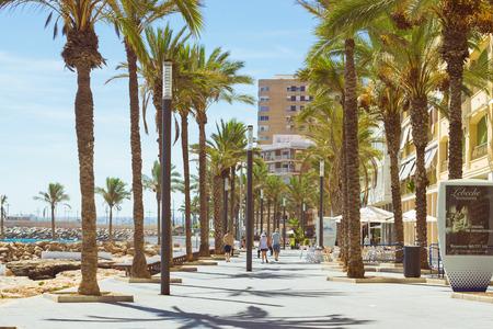 av: TORREVIEJA, SPAIN - SEPTEMBER 13, 2014: Coastal pedestrian street Av de los Marineros with tourist shops, cafes and restaurants. Nearby is Sunny Mediterranean beach, Torrevieja, Valencian Community, Spain