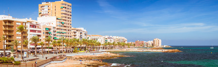 a bathing place: TORREVIEJA, SPAIN - SEPTEMBER 13, 2014: Sunny Mediterranean beach, Tourists relax on warm shore of sea on loungers under parasols. People bathe in crystal clear salty water of sea, Paseo Juan Aparicio, Torrevieja, Valencia, Spain