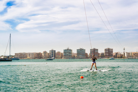 activ: TORREVIEJA, SPAIN - SEPTEMBER 13, 2014: Cute girl learns to surf on background of yachts and boats in La Bocana, Cable Ski, Torrevieja, Marina Salinas. Valencia, Spain