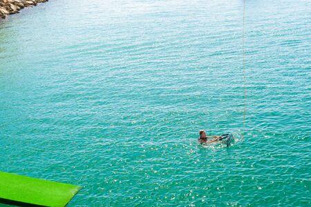 activ: TORREVIEJA, SPAIN - SEPTEMBER 13, 2014: Cute girl learns to surf in La Bocana, Cable Ski, Torrevieja, Marina Salinas. Valencia, Spain