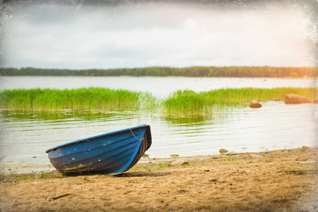 suomi: Blue rowing boat stands on a sandy shore in a quiet Bay of the Finnish Gulf. Area for summer camping in the woods. Hamina, Finland, Suomi Stock Photo