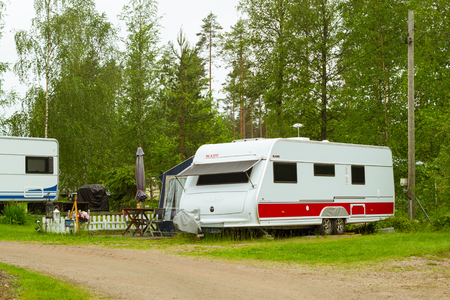 suomi: HAMINA, FINLAND - JUNE 13, 2014: Summer outdoor recreation, Scandinavian vacation in house on wheels. Camping vans and tents parked on a green meadow in campsite among trees. Purhon Campsite, Hamina, Finland, Suomi