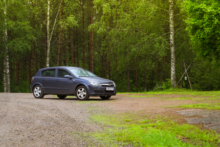 LAPPEENRANTA, FINLAND - JUNE 13, 2014: Summer outdoor recreation, Scandinavian vacation in house on wheels. Dark-blue Opel Astra H parked on a green meadow in campsite among trees. Palvaanjarven Campsite, Luumaki, Lappeenranta, Finland, Suomi Editorial
