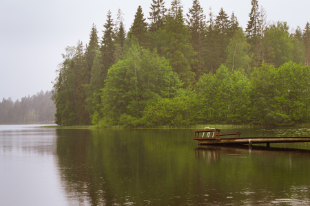 suomi: Cloudy summer day on the lake. Wooden boat pier overlooking the water and island. Area for summer camping in the woods. Palvaanjarven Campsite, Lappeenranta, Finland, Suomi