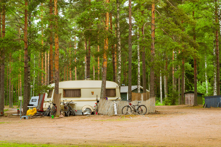 parked bikes: HAMINA, FINLAND - JUNE 13, 2014: Summer outdoor recreation, Scandinavian vacation. Camping vans and bikes parked in a wooded campsite among pine trees. Finnish Gulf. Area for camp in woods. Hamina, Finland, Suomi