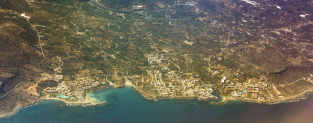 Seaside view of resort Crete island with hotels and beaches, aerial view from flight altitude of aircraft. Sun reflected from the water surface through the clouds. Mountainous landscape and roads-serpentines. Greece