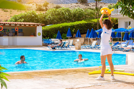 BALI, GREECE - APRIL 29, 2016: Animation at Resort hotel Atali Village 4 star. Cute girl in white beach suit conducts classes for tourists in water aerobics in pool with clean blue water. Editorial