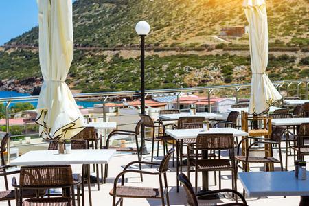 hotel resort: White tables with wicker chairs outside on veranda of restaurant, overlooking the Cretan sea. Resort hotel Atali Village 4 star, Bali, Rethymno, Crete, Greece