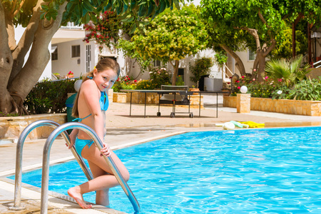 4 star: Cute little teenage girl in swimsuit standing at entrance to pool in middle of day. Relax and sunbathe by pool with clear blue water in Resort hotel Atali Village, 4 star. Bali, Rethymno, Crete, Greece