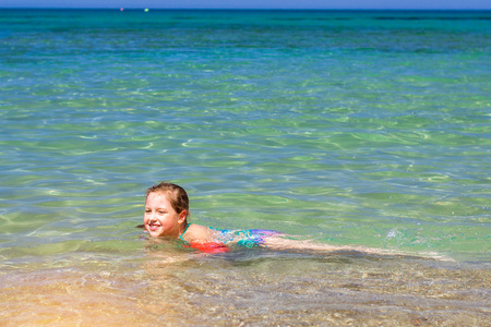 bathed: Cute happy girl child relaxing and bathed on the shores of Cretan sea in rescue arm cover. Sunny sandy Livadi beach in sea Bay of resort village Bali, Rethymno, Crete, Greece Stock Photo