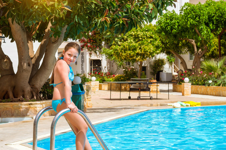 swim suit: Cute little teenage girl in swimsuit standing at entrance to pool in middle of day. Relax and sunbathe by pool with clear blue water in Resort hotel Atali Village, 4 star. Bali, Rethymno, Crete, Greece